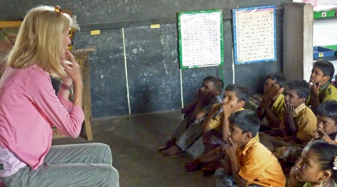 Teaching volunteer teaches her class a song to help them with their English pronunciation in India.